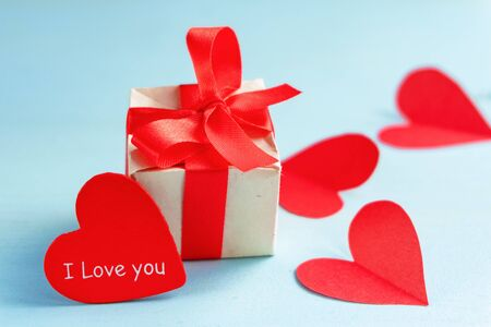 Gift box, heart with text I love you and hearts cut out of paper on a blue background.