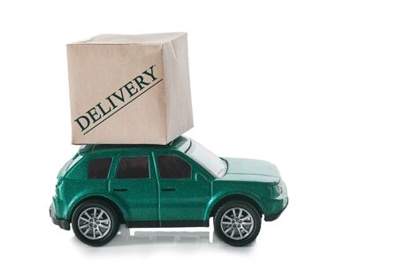 Cardboard box on the roof of the car with the text - delivery. Delivery concept