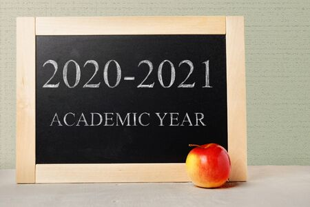 School board with text academic year 2020 2021. Background School blackboard and apple