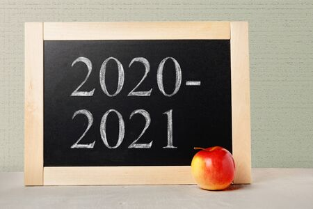 School board with numbers 2020 2021. Background School blackboard and apple. Beginning of the school year