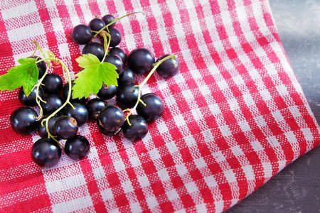 Ripe fresh black currant with green leaves on a red napkin. 免版税图像