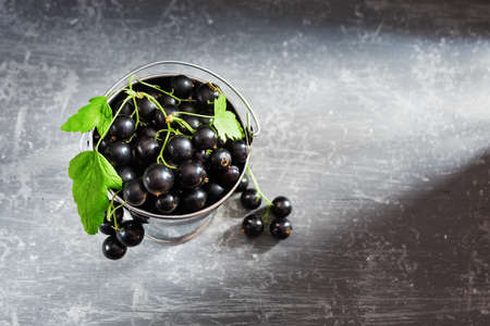 Black currant berries in a bucket on   gray