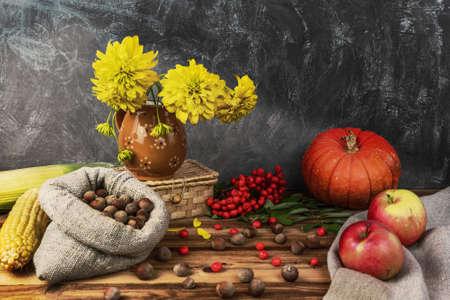 Autumn still life. Corn, apples, hazelnuts, red pumpkin, flowers in a vase, wicker box, rowan berries on a wooden background.