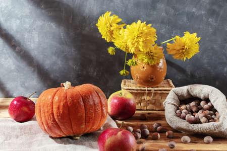 Autumn still life. Apples, hazelnuts, red pumpkin, flowers in a vase, wicker box on a wooden background Zdjęcie Seryjne
