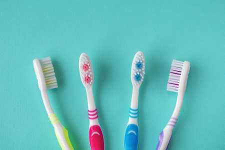 Clean toothbrushes of different colors on a blue background. 免版税图像