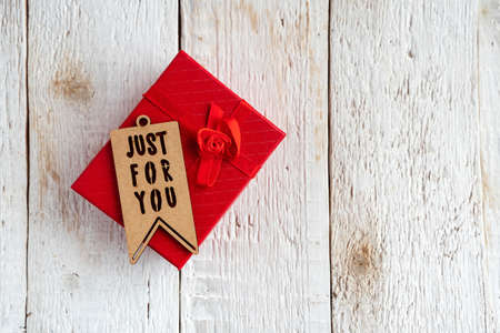 Red gift box and text just for you on a white wooden background.