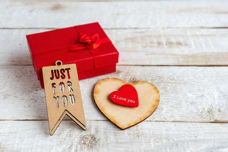 Red gift box and two hearts on a white wooden background. Texts I love you and just for you 免版税图像