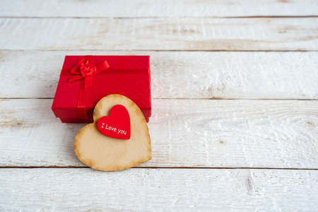 Red gift box and two hearts on a white wooden background. Text I love you