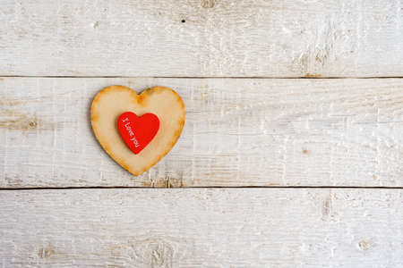 Two hearts, red and wooden on an old white background. Text I love you. Valentine day 免版税图像