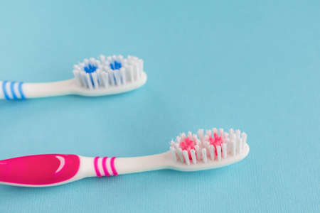 Two new toothbrushes on a blue background.