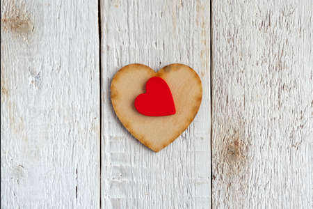 Red and wooden hearts on an old white background.