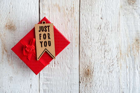 Gift red box and tag with text just for you on an old white wooden background.