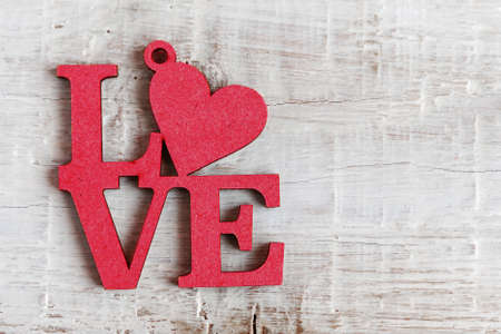 Red letters with a heart made of wood with the text Love on a white wooden background.