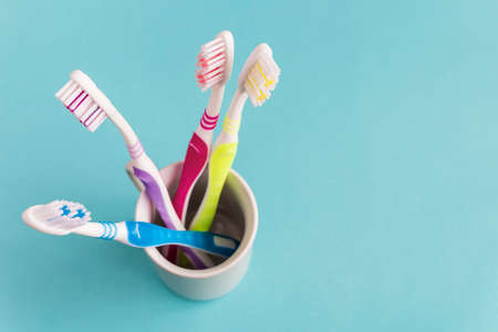 Toothbrushes in a ceramic holder on a blue background
