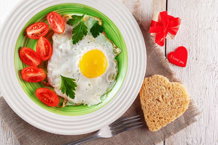 Fried egg with tomato slices, heart-shaped bread, gift box and red heart. 免版税图像