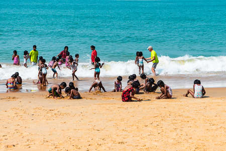 India, Goa - February 14, 2019: Indian children on the shore of the Arabian sea swim and play on the sand.