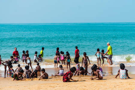India, Goa - February 14, 2019: Indian group of children on the shore of the Arabian sea swim and play on the sand. 新闻类图片