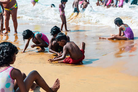 India, Goa - February 14, 2019: Indian of children boys and girls on the shore of the Arabian sea swim and play on the sand. 新闻类图片