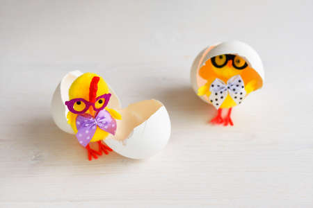 Two chicks with eggshells. Toy chickens with glasses with bows. 免版税图像