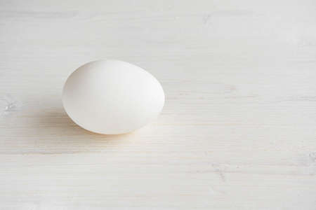 Single white egg on a white wooden background.