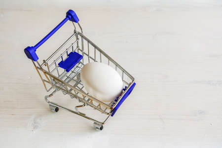 Single white chicken egg in small shopping trolley. Mini cart with egg on wooden white background ..