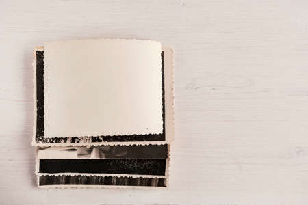 A stack of old photos with an empty reverse side on a wooden background. Copy space
