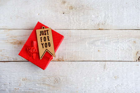 Red gift box on white wooden background. Tag with text just for you. 免版税图像