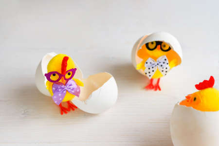 Three toy chickens with glasses in eggshells on a white background. 免版税图像