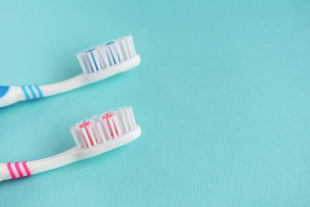 Two clean toothbrushes on a blue background. Copy Space.