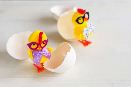 Two yellow chicken toys with glasses and eggshells on a white background. 免版税图像