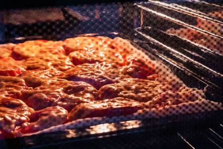 Food in a closed oven. Food with tomatoes and cheese baked in the oven.