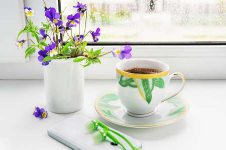 A cup of coffee, flowers of the field pansies, phone and headphones on the windowsill.
