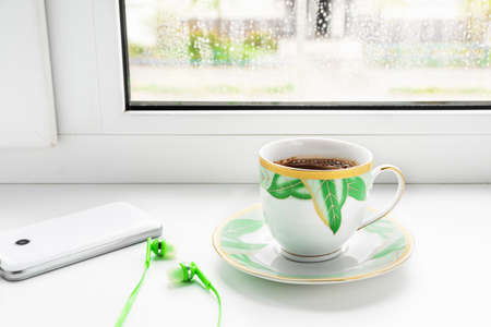 A cup of coffee, phone and headphones on the windowsill.