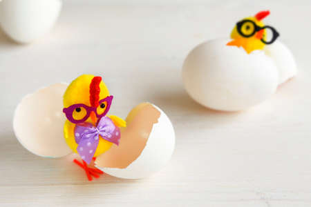 Chicken toys in glasses with a bow. Chick with egg shells.
