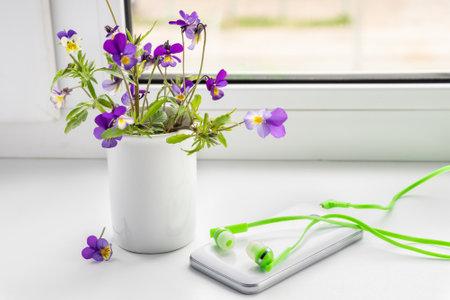 Wildflowers, phone and headphones on the windowsill.
