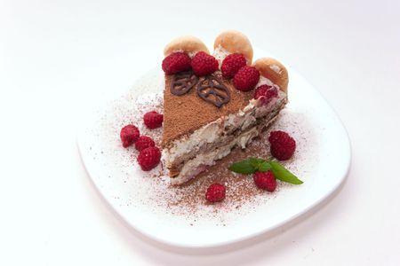 Delicious Italian dessert tiramisu decorated with raspberries, chocolate leaves and mint photo