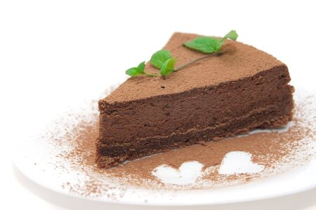 cheesecake: Chocolate cheesecake decorated with mint sprig and hearts isolated on white Stock Photo