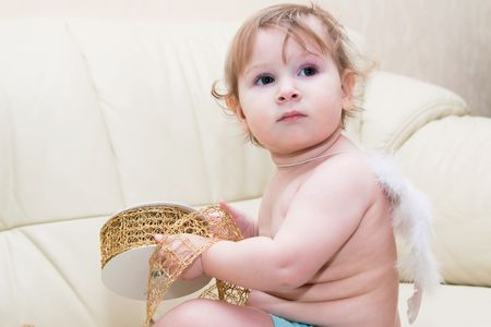 Little baby angel with wings sitting at light sofa and holding gold ribbon photo