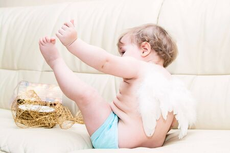 Little baby angel with wings sitting at light sofa showing its hand and leg with present and gold ribbon on background photo