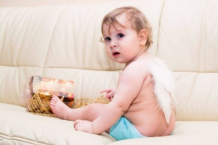 Little baby angel with wings sitting at light sofa with present and gold ribbon on background photo