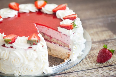 cake decorating: Birthday cake with fresh strawberries and white cream roses on wood background