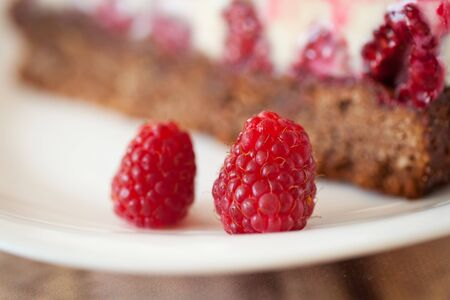 custard slices: Two raspberries close-up with cheesecake on background Stock Photo