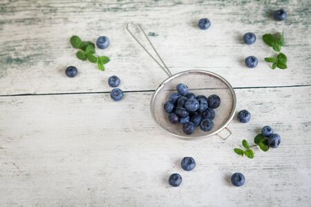 a place for the text: Top-view of blueberries or bilberries in a metal strainer with mint and a place for text Stock Photo