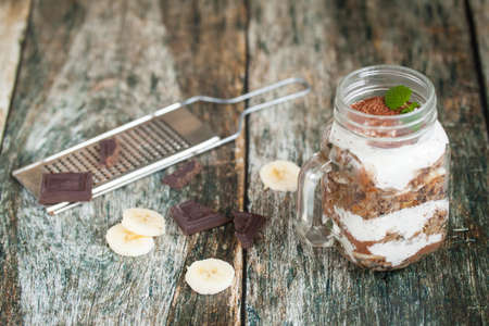 choco: Healthy breakfast in a glass mason jar. Served with chocolate and banana on wooden table. Metal grater for choco Stock Photo