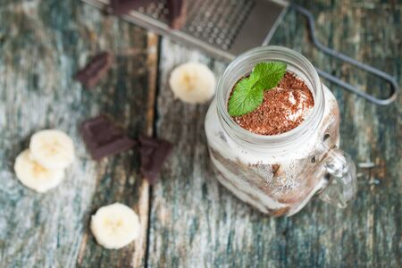 metal grater: Healthy breakfast in a glass mason jar. Served with chocolate and banana on wooden table. Metal grater for choco Stock Photo