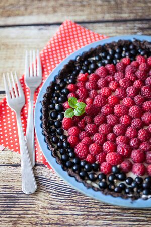 black currants: Homemade tart pie with cream, raspberry and black currants, decorated with mint on orange fabric and wooden table background Stock Photo
