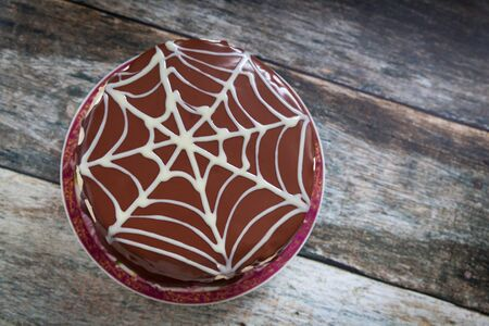 Chocolate cake with spider web Halloween decoration on wood background