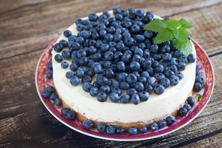 custard slices: Cheesecake with ripe blueberries and fresh mint on wood background