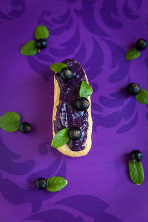 black currants: Eclair with cream and black currants on violet background