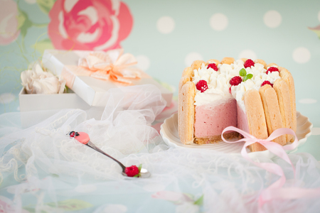 patisserie: Tiramisu cake charlotte decorated with raspberry with pink ribbon and funny spoon on a pink & blue floral background